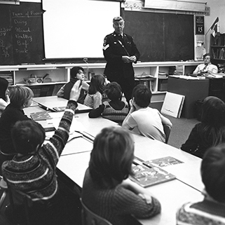 An officer stands in front of a classroom of small children