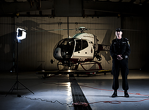 A man stands next to a bright light and a helicopter