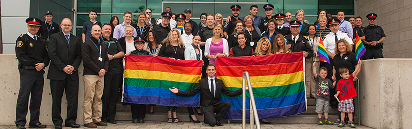 A group of officers and citizens stand together with two rainbow flags