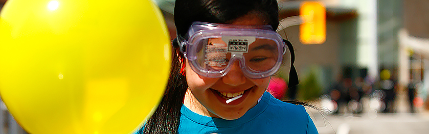 A young girl wears goggles and holds a yellow balloon