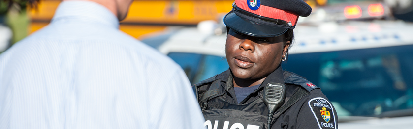 An officer speaks to a man in front of a school bus
