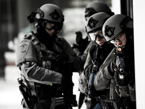 A group of officers wearing grey equipment readies their guns