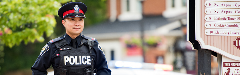 A man in a police uniform stands in front of a streetscape