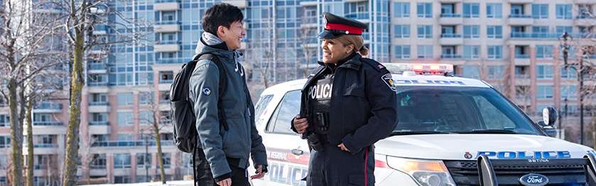 A woman in a police uniform smiles and speaks to another man in front of a police cruiser