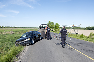 A man in a uniform holds a bicycle next to a car that in a ditch
