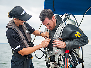 A woman helps a man adjust a black dive suit