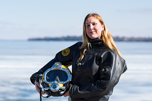 A blonde woman stands in front of a frozen lake in a black rubber suit.