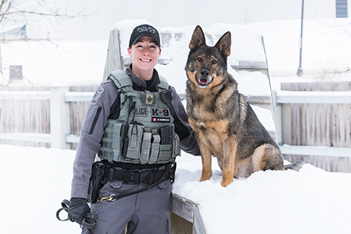 A woman in a police uniform smiles next to a large dog, in a snowy yard.