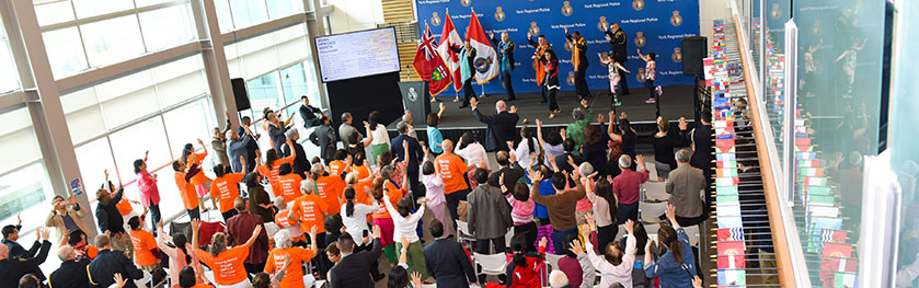 A group of five adults and two kids dance on stage in front of a large crowd at police headquarters