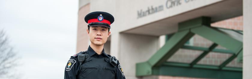 An officer stands in front of a police station