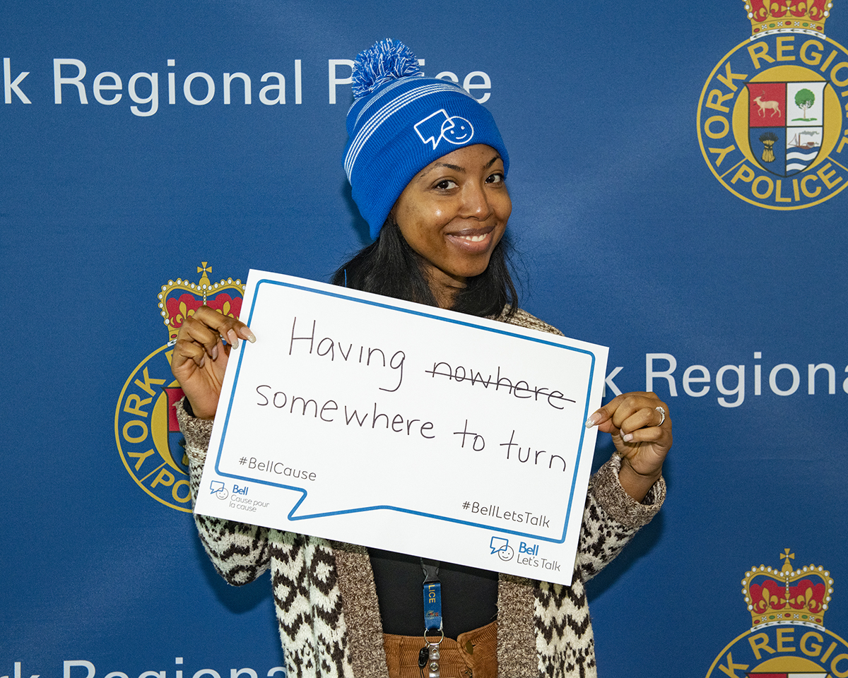 A female civilian smiling and wearing a Bell Let's Talk toque and holding a sign