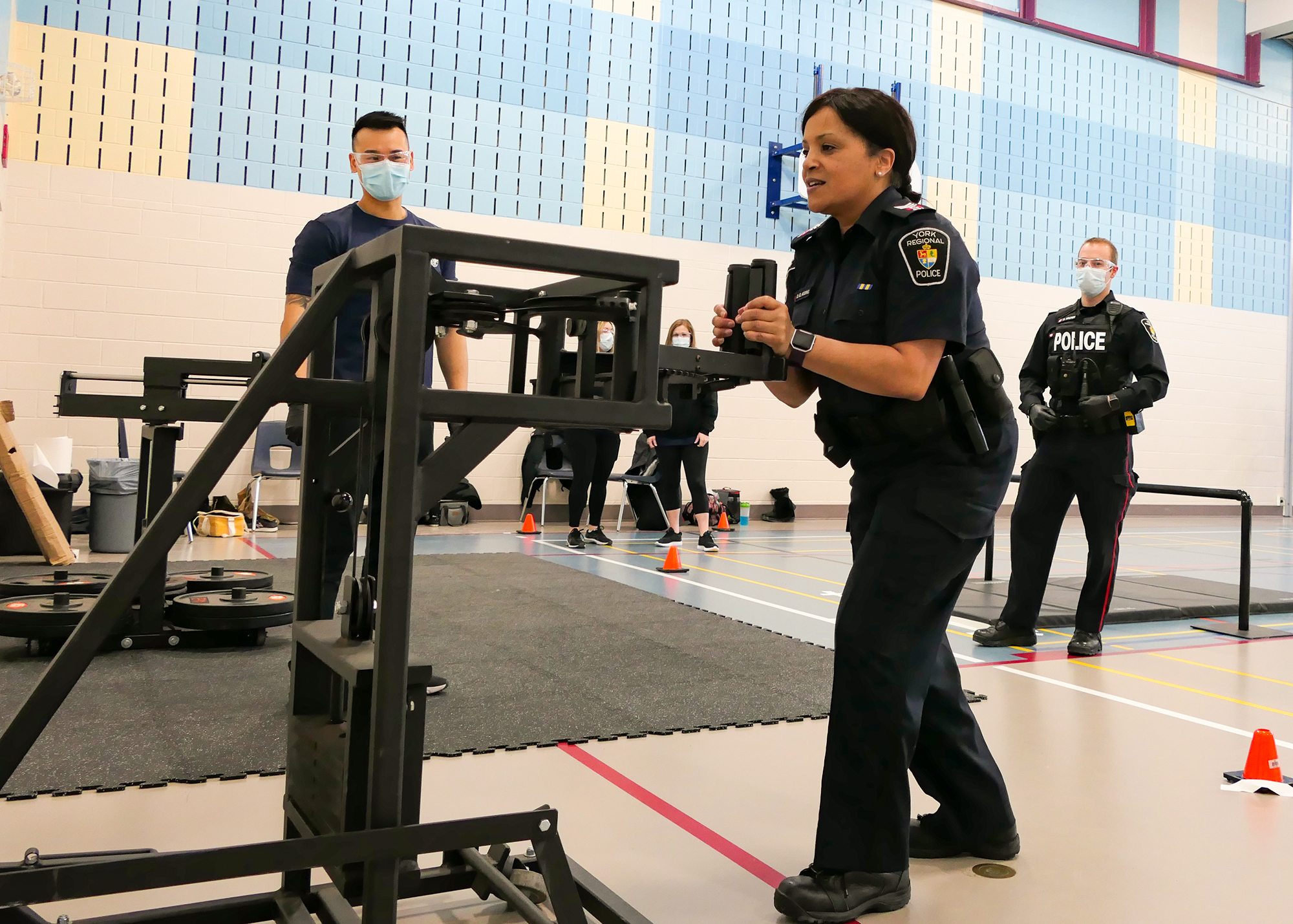 A female officer showing how to properly complete a component of a fitness test