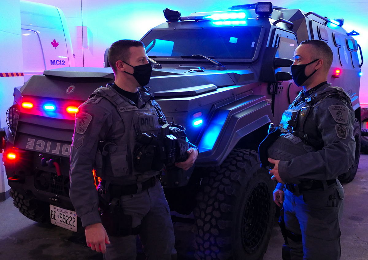 Two officers stand in front of an emergency response vehicle