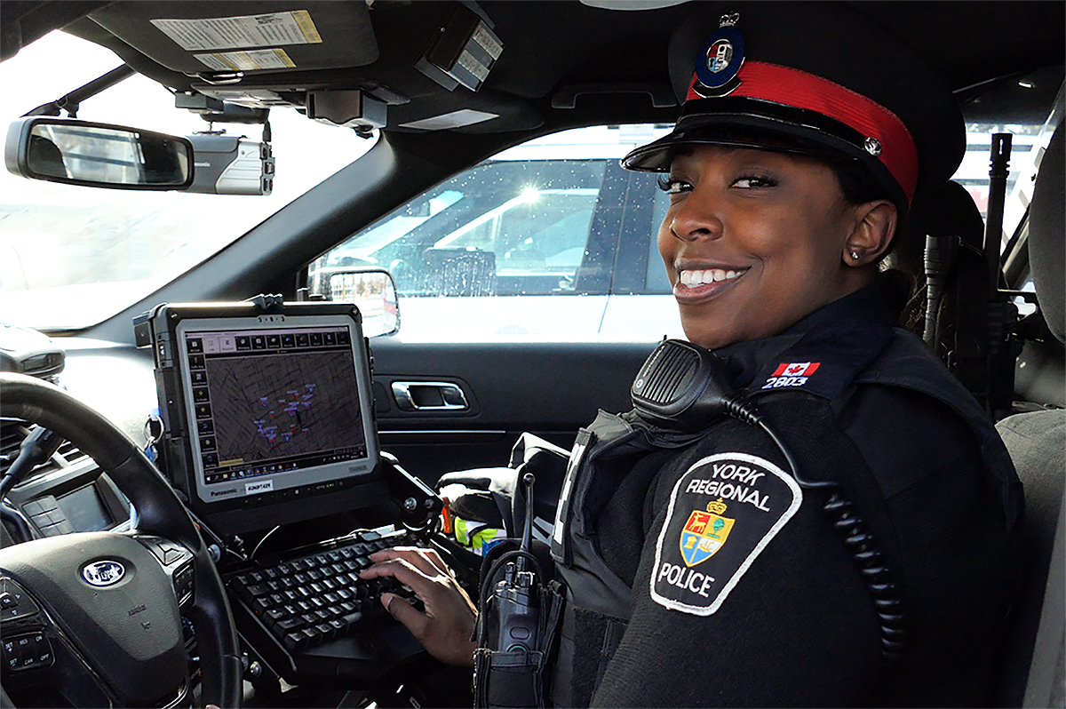 A female officer sitting in a cruiser