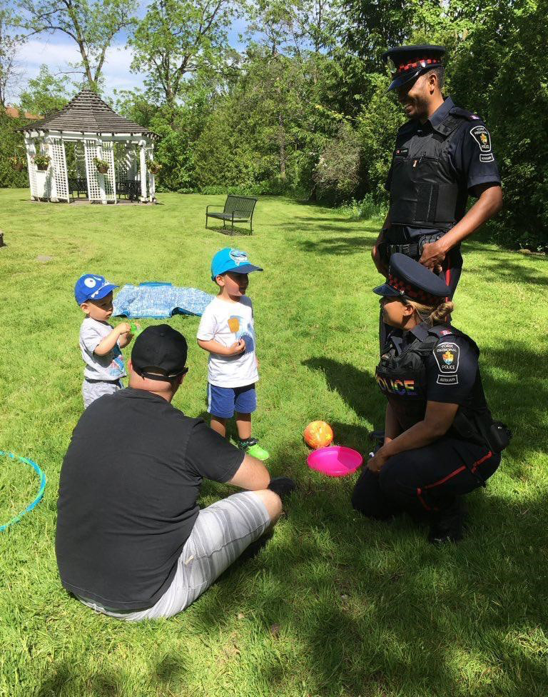A female and male auxiliary officers talk to a child