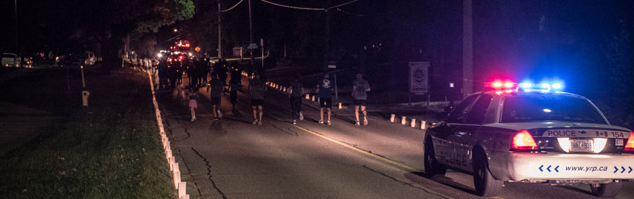 A line of runners with candles lighting the route and a police cruiser escorting them