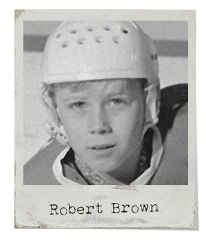 A blonde-haired boy wearing a white hockey helmet