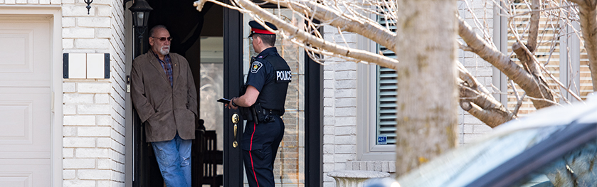A man in a police uniform speaks to another man at the front door of a house