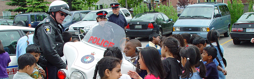 An officer on a motorcycle talks to a group of students