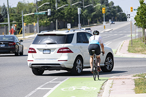 A cyclist rides in a green bike lane while a car turns in his path