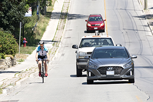 A cyclist rides near the curb while cars pass