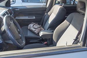 A brown purse sits on a car seat