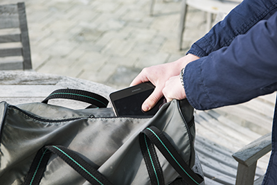 A person pulls an electronic device out of a duffel bag.