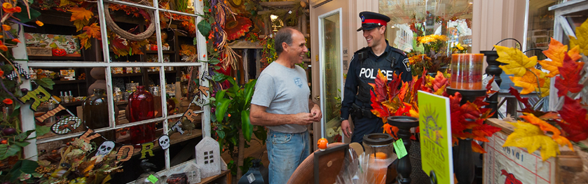 An officer and man stand in a decorated shop