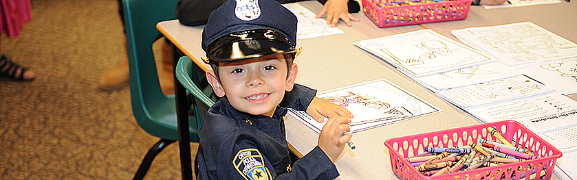 A child in a police costume colours with crayons