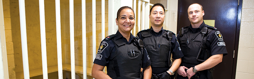 Three officers in front of a white bars