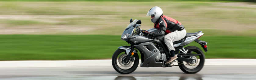 A man on a silver motorcycle speeding