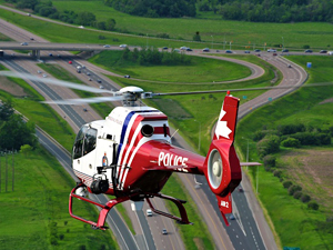 A helicopter flies over a highway