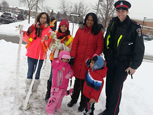 An officer stands with children smiling
