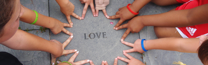 Children's fingers form a circle with the word love in the middle