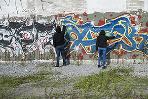 A pair of people in black hoodies spray paint a wall