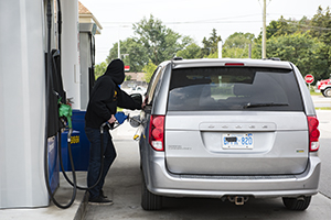 A man in a black hoodie pumps gas into a van with a shrouded license plate