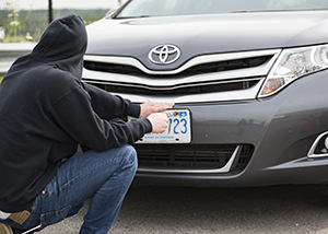A person in a black hoodie holds a screwdriver near a licence plate