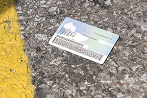 A piece of identification lies on an asphalt surface