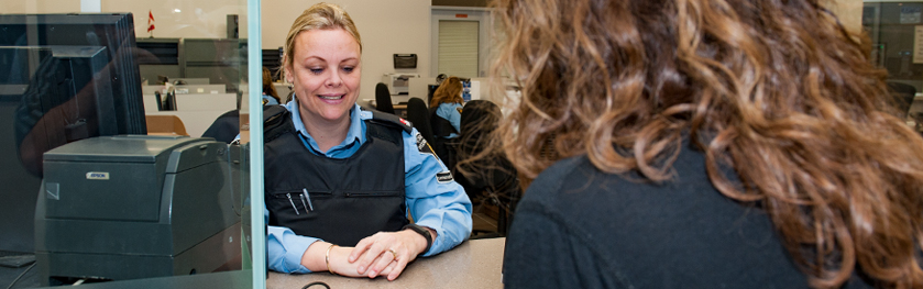 A woman in a police uniform smiles behind a counter